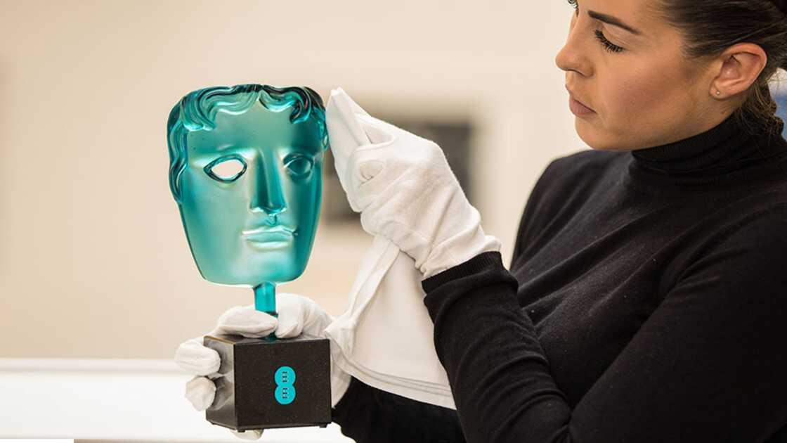 Woman dusts off aqua BAFTA mask award