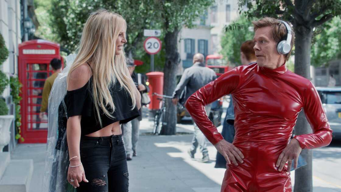 Kevin Bacon wearing red catsuit next to Britney Spears