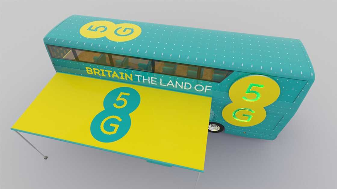 A double-decker bus with the slogan 'Britain, Land of 5G'