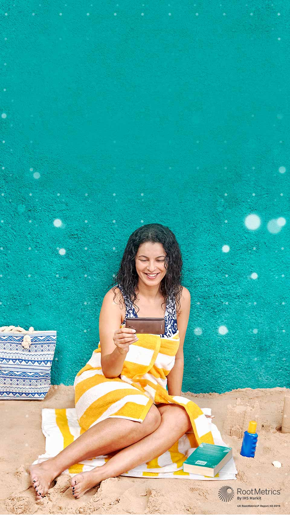 Woman on the beach holding a mobile device