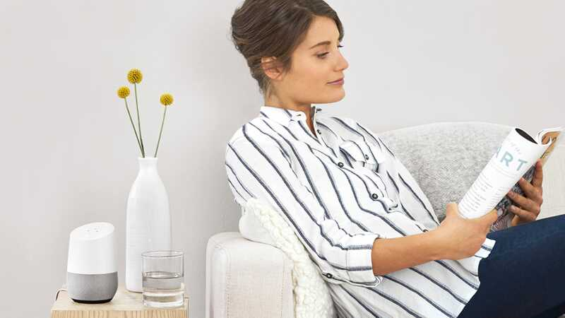 Woman reading magazine next to smart home device