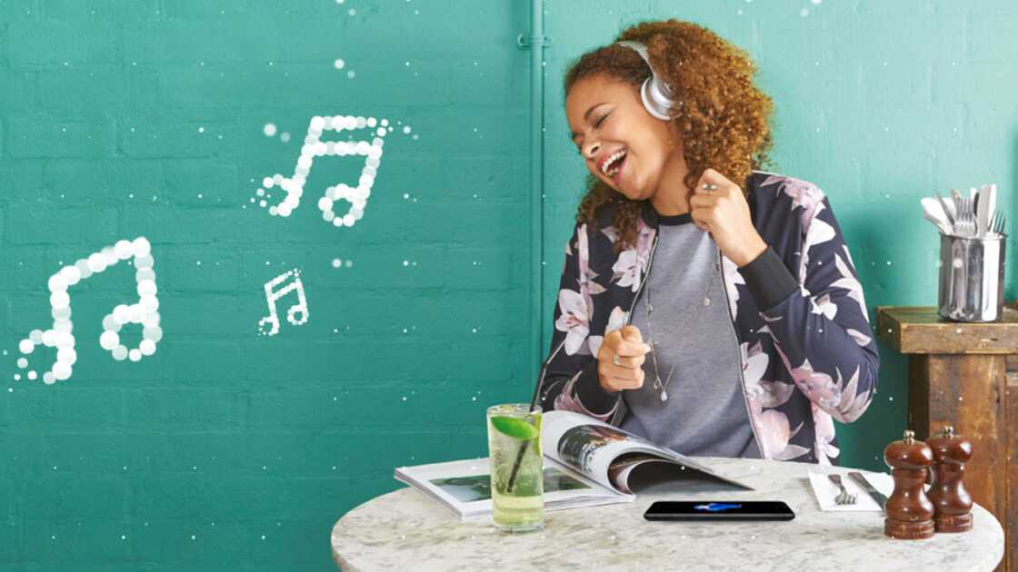 A woman sat at a table wearing a floral jacket and grey t-shirt dancing and singing to music playing on her headphones