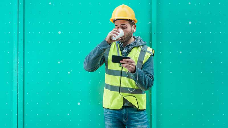 An engineer has a drink while watching content on his phone during a break