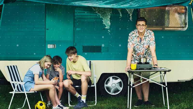A family taking cover from the rain under a caravan awning looking at a smartphone