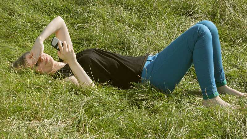 Woman with phone lying on grass