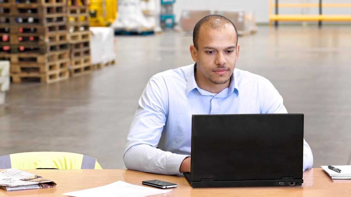 Man on laptop in warehouse