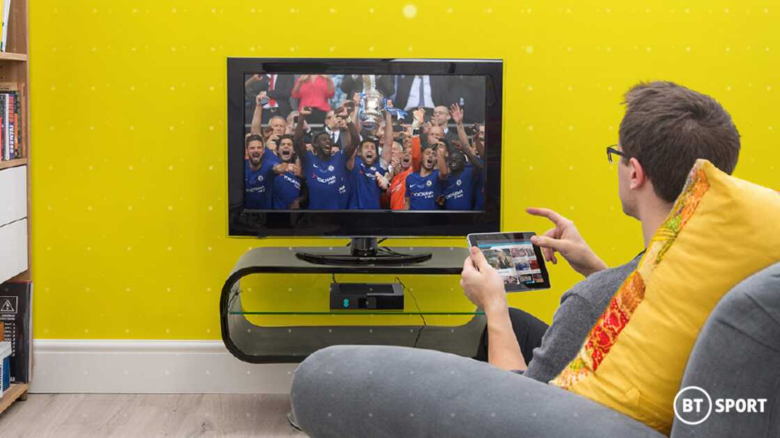 A man sat on a grey chair holding a tablet and watching a football match on the TV